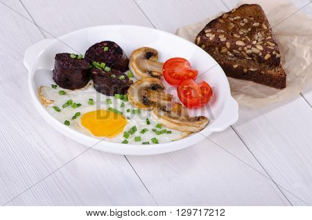 Breakfast - fried egg with mushrooms tomatoes and black pudding