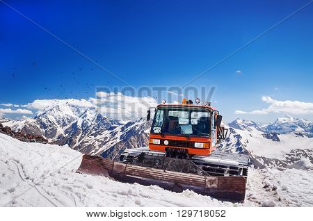 Snow machines in the Caucasus Mountains clear sunny day with birds flying in the sky