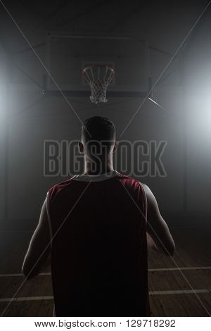 Portrait of basketball player front the back in front of a basket on a gym