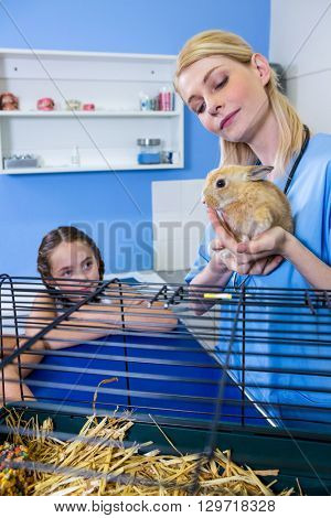 A woman vet bringing a rabbit in front of children