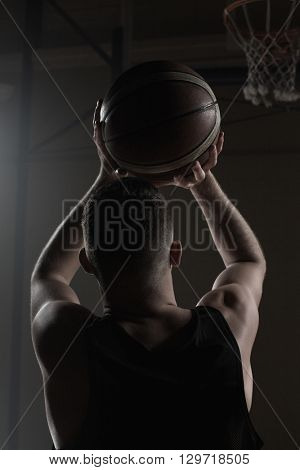 Portrait front the back of basketball player trying to put a basket on a gym