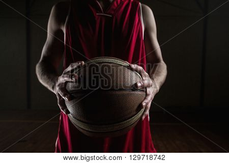 Close up on basketball player holding a ball on a gym