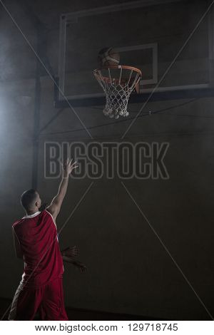 Portrait of basketball player scoring a goal on a gym