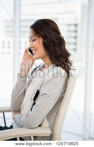 A businesswoman has a phone call in her office