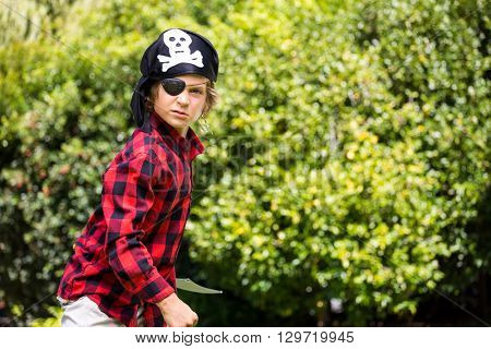 A kid with a costume of pirate is waiting the fight in a garden