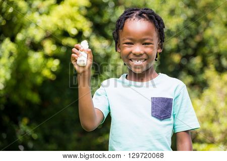 Boy showing his asthma inhaler in the park