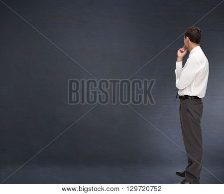Thoughtful classy businessman looking away against black background