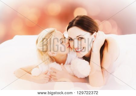 Cute little girl kissing her mother against glowing background