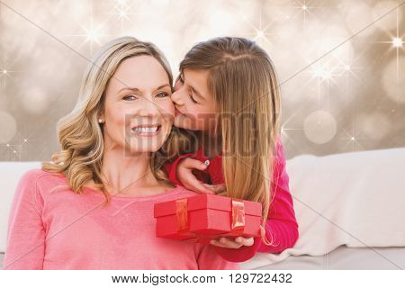 Smiling mother being kissing by daughter against shimmering light design on grey