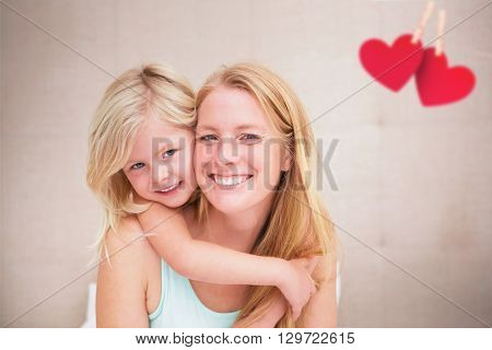 Hearts hanging on a line against cute little girl and mother on bed