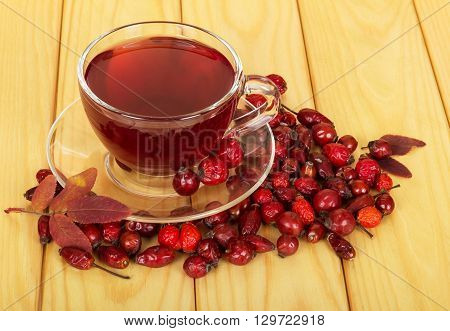 Rosehip berries and hot tea on a wooden table