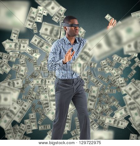 Blindfolded businessman with arms out against blue vignette background