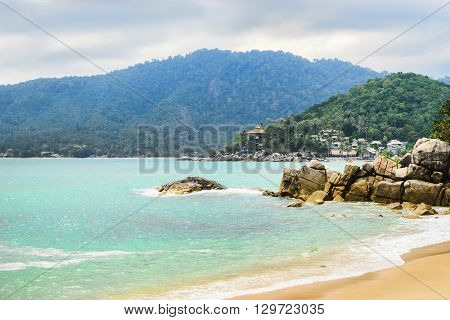 Beautiful bay with crystal clear water. An island with tropical forest on the background.