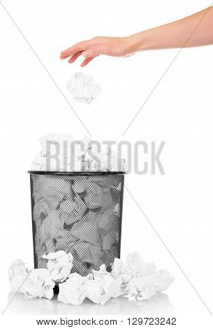 Hand throwing crumpled paper into the office trash isolated on white background
