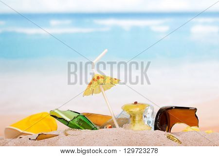 Debris and broken glass on a sunny beach