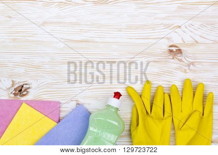 Detergent, rags and latex gloves on wooden background