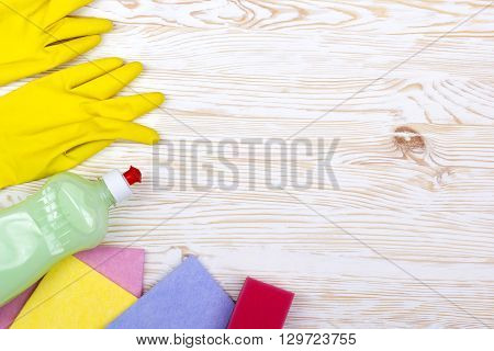 sponge, rsgs and a bottle of detergent on wooden background
