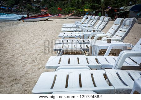 White loungers on the beach with white sand in Thailand