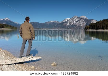 man stands on waters- edge of a lake