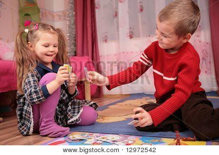 twee kinderen spelen kaarten in de speelkamer
