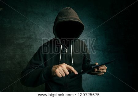 Faceless hooded unidentifiable male person using tablet computer internet hacker and online security concept.