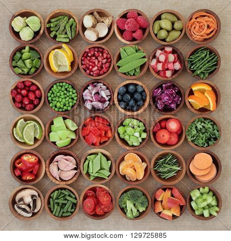 Super food sampler for paleolithic diet with fresh vegetables and fruit in wooden bowls over brown paper background. High in vitamins, antioxidants, minerals and anthocyanins.