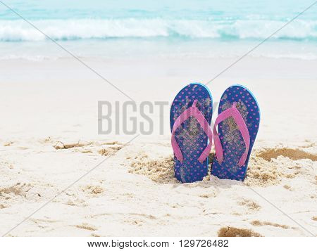 Blue flip flop on summer sand beach