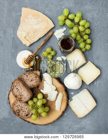 Cheese appetizer selection or wine snack set. Variety of italian cheese, green grapes, bread slices and honey on round wooden board over grey concrete backdrop, top view, vertical