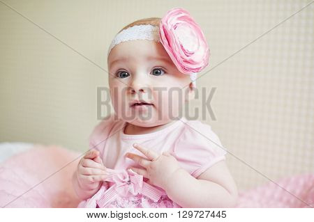 portrait of cute little baby girl with pink bow flower on her head.