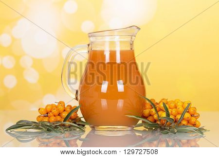 Sea buckthorn juice in a jug and branches on a yellow background