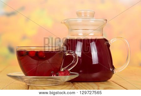 Vitamin tea from rose hips in cup and teapot on wooden table