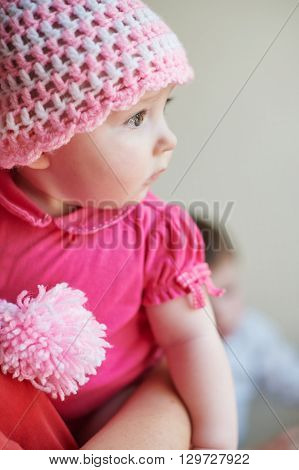 little baby girl in a knitted hat on hands at mum.