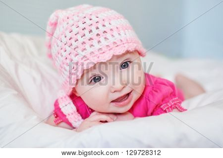 newborn baby girl in pink knitted hat on the bed.