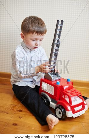 little boy playing red toy machine in room.