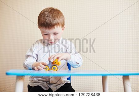 Little boy playing with colored toy car on a table.