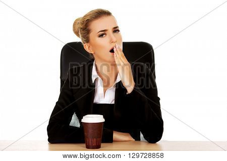 Yawning businesswoman drinking coffee from paper cup behind the desk