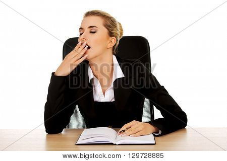 Yawning businesswoman writing note by a desk