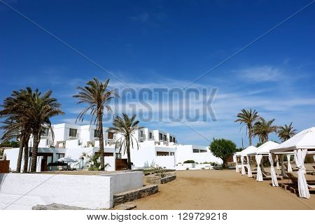 HERAKLION CRETE GREECE - MAY 13 2014: The blue sky modern buildings of villas and palms on the terrain of luxury class hotel on the Mediterranean coast of Crete May 13 2014 Greece.