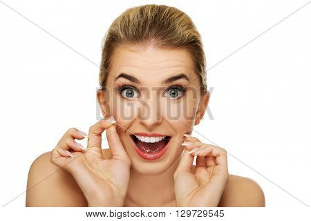 Young woman flossing her teeth.