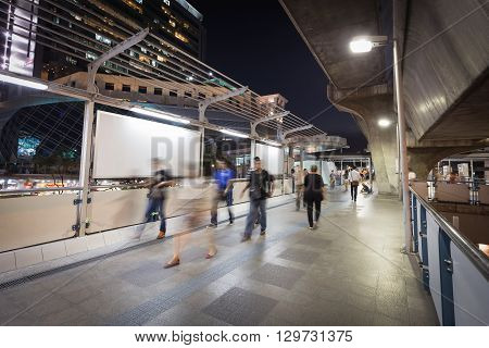 Bangkok Thailand - May 10 2016: Blurry walking people on sky walking path in Bangkok (called Siam) at night after office hour.