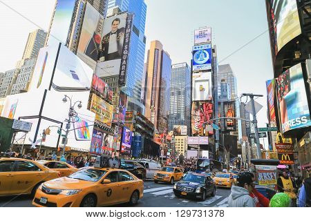 New York USA - May 20 2014: Crowd and traffic in time square area. Many yellow cabs on the road. Tall buildings and billboards are around this place.