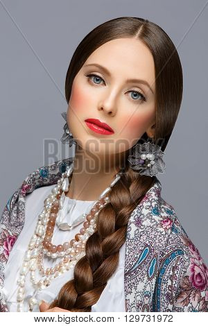 Beautiful young russian woman with very long braid in traditional shawl. Red lips. Over grey background.