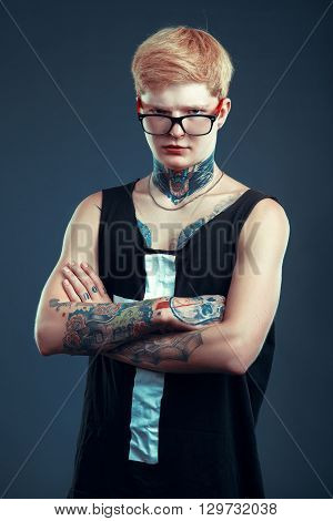 A Young Blond Man In Glasses With A Pierced Nose And A Tattoo Is Back. The Concept Of Thoughtfulness