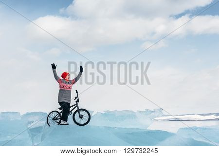 Girl standing on a bmx on the beautiful and dangerous ice and enjoys a successful campaign. Ice the deepest lake in the world. This is Lake Baikal.
