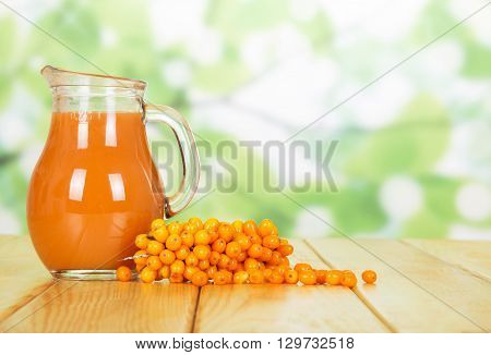 Jug with sea buckthorn juice on the abstract green background
