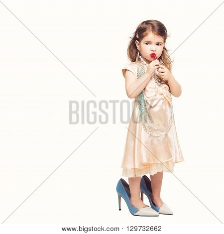 Beautiful small girl in dress and mother's high heels applying red lipstick. Isolated over white background. Copy space.