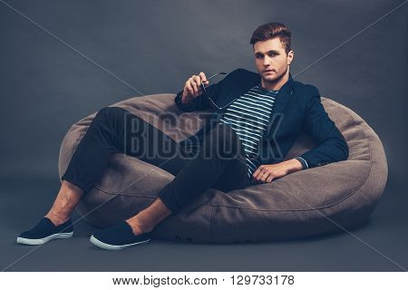 Stylish and handsome. Confident young handsome man looking at camera while sitting on beanbag against grey background