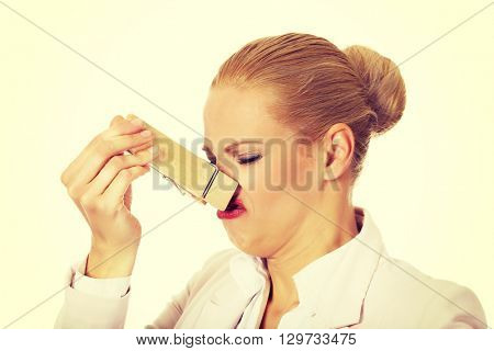 Young business woman with huge clothespin on her nose. Stinks concept