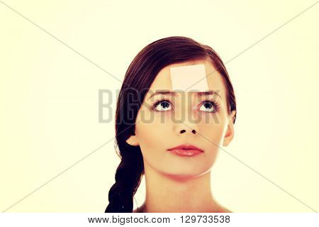 Young woman with sticky notes on forehead