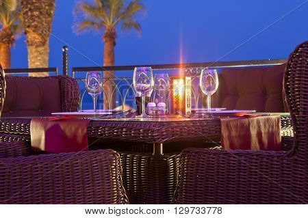 Served table in a restaurant outdoors at evening time.